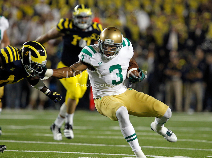 Notre Dame wide receiver Michael Floyd (3) tries to avoid a tackle from Michigan cornerback Courtney Avery, left, in the second quarter of an NCAA college football game, Saturday, Sept. 10, 2011, in Ann Arbor, Mich. Michigan won 35-31. (AP Photo/Tony Ding)