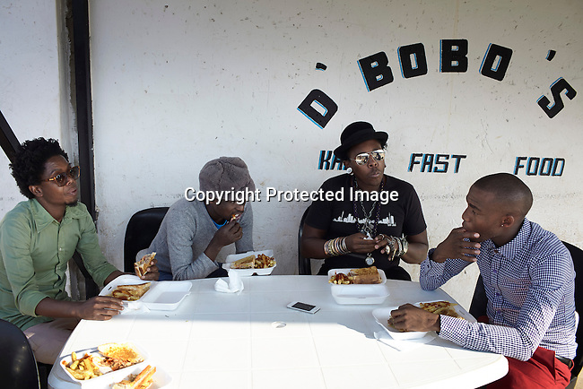 SOWETO, SOUTH AFRICA MAY 21: Members of the designer group Smarteez eat lunch before a photo shoot on May 21, 2013 in Kliptown section of Soweto, South Africa. They did a photo shoot together with a new collection. The members are Teekay Makwale, Floyd Avenue. Sibu Sithole and Lethabo Tsatsinyane. They are trying to break into the local fashion scene. Soweto today is a mix of old housing and newly constructed townhouses. A new hungry black middle-class is growing steadily. Many residents work in Johannesburg but the last years many shopping malls have been built, and people are starting to spend their money in Soweto. (Photo by: Per-Anders Pettersson)