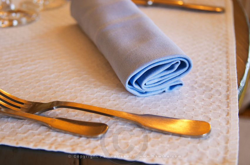 In the restaurant in the Domaine de Cabasse hotel and restaurant. Provencal colours, Detail of rolled up blue napkin and forks with white table mat. Domaine de Cabasse Hotel Restaurant, Alfred and Antoinette Haeni, Séguret, Seguret Cote du Rhone Vaucluse Provence France Europe