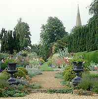A pair of Grecian urns marks a gravel path which at the centre of the garden