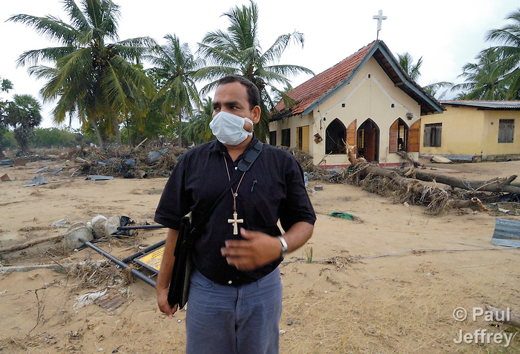The Rev. Nadarajah Arulnathan, a Methodist pastor in Passikudah, Sri Lanka, stands in front of his church, damaged by the South Asian tsunami. All around the church, homes were smashed and land mines washed loose from a nearby army base. As a result, many decaying bodies mixed in the debris had yet to be removed. Arulnathan, who lost 18 relatives to the disaster, led a local committee of church leaders coordinating the response in the region of the National Christian Council of Sri Lanka, a member of Action by Churches Together (ACT) International. Churches and NGOs provided almost all of the relief to tsunami victims in the area. The December 26, 2004, tsunami left devastation behind along most of the island nation's coastline.