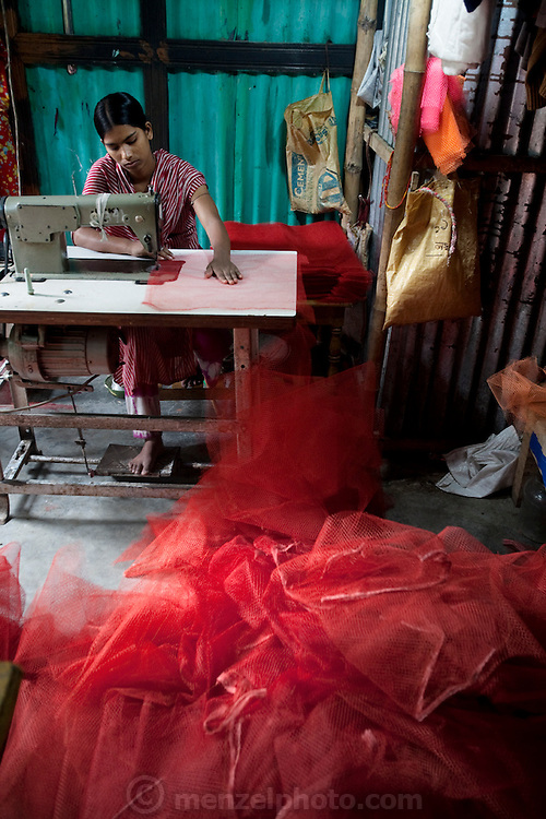A woman sews mesh bags for sale in the village of Bari Majlish, an hour outside Dhaka. (From the book What I Eat: Around the World in 80  Diets.) The  Bangladesh Rehabilitation Assistance Committee (BRAC), has provided micro-loans to village women making mesh bags.