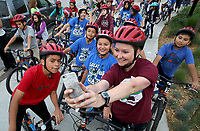 NWA Democrat-Gazette/DAVID GOTTSCHALK  Allison Engelbert, an intern at George Elementary School from the University of Arkansas, holds up her camera Wednesday, May 10, 2017, to take a photograph with students from the school on Shiloh Square in Springdale. Students from the school participated in the second annual Springdale City-Wide Walk and Bike to School Day. The students rode from the square to the school on the Razorback Regional Greenway. Mayor Doug Sprouse read a proclamation before the start of the ride.