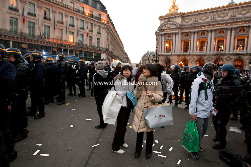 Two Japanese tourists find themselves surrounded by riot police after exiting a subway station in the middle of a protest by several thousand people against Israel's military offensive in the Palestinian Gaza Strip, Place de l'Opera in Paris, France, 17 October 2009.