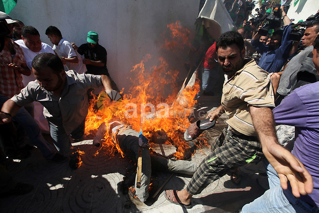 Palestinians burn the U.S. flags during a demonstration against the controversial film 'Innocence of Muslims' in Gaza city, on September 14, 2012. The controversial low budget film reportedly made by an Israeli-American which portrays Muslims as immoral and gratuitous, sparked fury in Libya, where four Americans including the ambassador were killed on Tuesday when a mob attacked the US consulate in Benghazi, and has led to protests outside US missions in Morocco, Sudan, Egypt, Tunisia and Yemen. Photo by Majdi Fathi