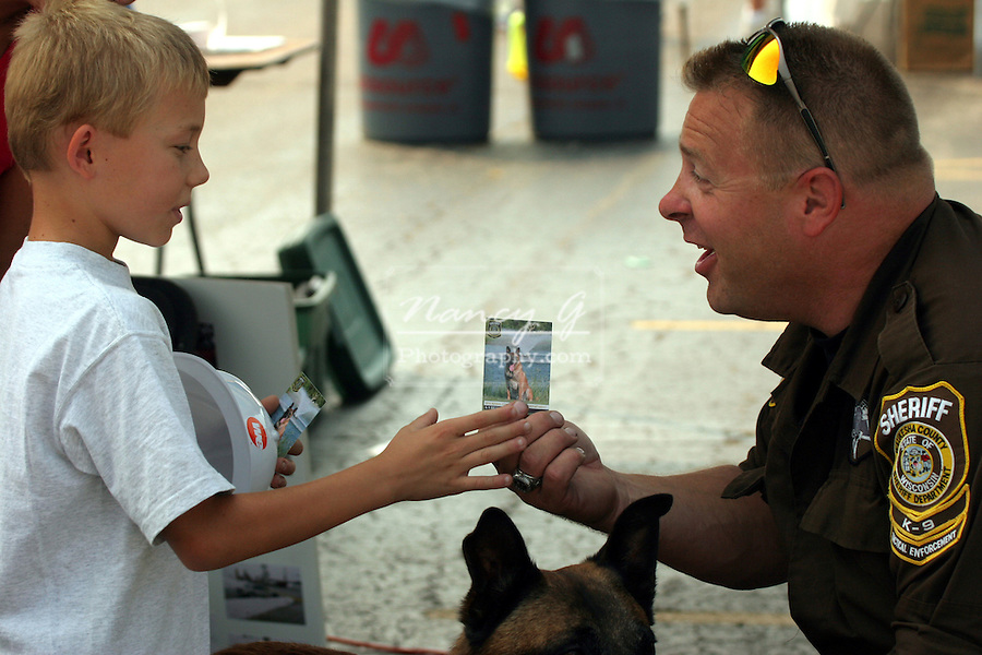 K-9 Unit County Sheriff and K-9 dog talking to boy about the police dogs and giving him an educational trading card.