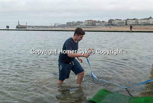 Greek community Uk. Margate Kent.  The Blessing of the Sea ceremony to celebrate   Epiphany on 6th January. A young male member of the Greek Orthodox Church is chosen to collect the decorated cross that is thrown into the sea.