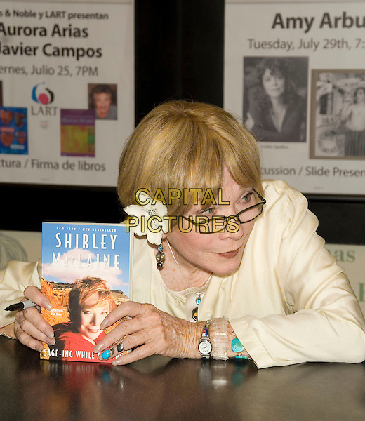"SHIRLEY MacLAINE.""Sage-ing While Age-ing"" book signing.at the Barnes & Noble -  Lincoln Triangle, New York, NY, USA, .July 22, 2008..half length sitting down cream jacket  flower in hair glasses holding book ring.CAP/LNC/TOM.©LNC/Capital Pictures"