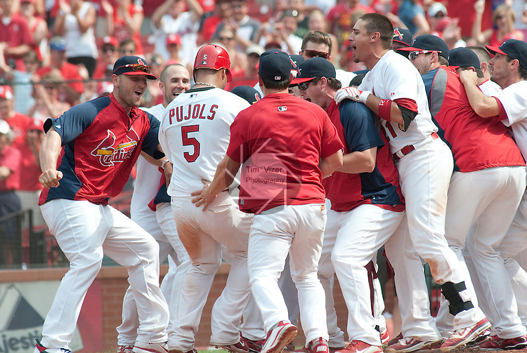 05 June 2011                 Cardinals teammates surround first baseman Albert Pujols as he crosses home plate after hitting the game-winning home run in the bottom of the tenth inning. The St. Louis Cardinals defeated the Chicago Cubs 3-2 in ten innings on Sunday June 5, 2011 in the final game of a three-game series at Busch Stadium in downtown St. Louis.