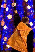 Kiev, Ukraine, 28/12/2004..The third and final round of Ukraine's disputed Presidential election. Supporters of candidate Viktor Yushchenko continue to demonstrate in the city centre. A demonstrator waves a victory salute with Christmas tree behind..
