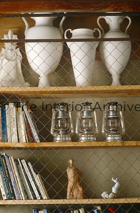 A collection of antique urns, hurricane lanterns and small figurines is displayed on the shelves of the living room bookcase