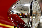An antique fire truck is seen in the reflection of a headlight of another antique fire truck in the Auxiliary garage of the Clifton Heights Fire Company in Clifton Heights, Pennsylvania.
