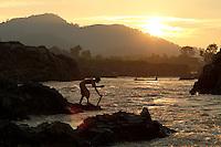 Fisherman building up his fishing trap at Somphanit fall, Khone falls, Laos-2010