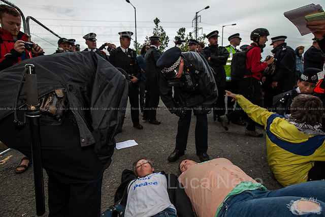 "London, 08/09/2013. Hundreds of protesters held a demonstration outside the east entrance of the ExCel Centre in East London to protest against the world's largest arms trade fair, where international military manufacturers exhibit their products. The trade fair has come under scrutiny various times in the past as Amnesty International campaigners and journalists have discovered internationally banned products (for example cluster bombs munitions and human restraints equipment) on sale. This action (the first of 15 events) was organised by the ""Stop the Arms Fair Coalition"", which includes the ""London Campaign Against the Arms Trade"" (CAAT), ""Disarm DSEi"", ""East London Against Arms Fairs"", ""Occupy London"" and ""Quakers for Peace"". Several demonstrators were arrested."