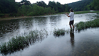 NWA Democrat-Gazette/FLIP PUTTHOFF <br /> Silcott catches a King River smallmouth bass in the rain June 9, 2016.