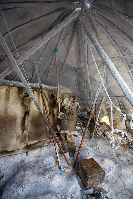 Natasha Nomro, a Chukchi woman, removing frost from the inside of her Yaranga (traditional tent). Chukotskiy Peninsula, Chukotka, Siberia, Russia.