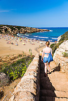 Calamosche Beach, tourist walking down the steps, near Noto, Vendicari Nature Reserve, South East Sicily, Italy, Europe. This is a photo of a tourist walking down the steps to Calamosche Beach near Noto in the Vendicari Nature Reserve, South East Sicily, Italy, Europe.