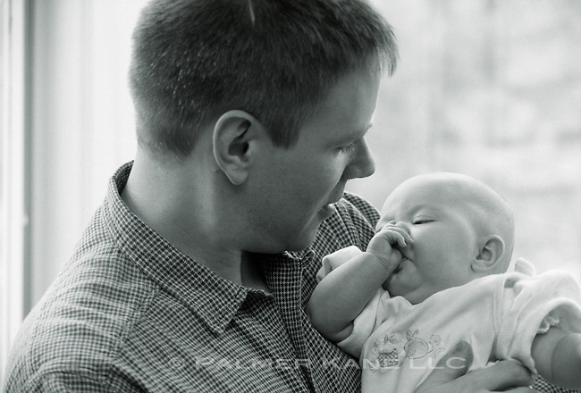 Baby in mans's arms sucking its thumb
