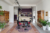 A converted shoe factory blends old world flavour with warehouse edge. In the dining room, Vitra Tulip chairs and table stand on top of one of the dozen vintage rugs that carpet the residence. On each side, early century Andalusian Bargueño. At the back of the room, the kitchen bar is by Ghassan Salame.