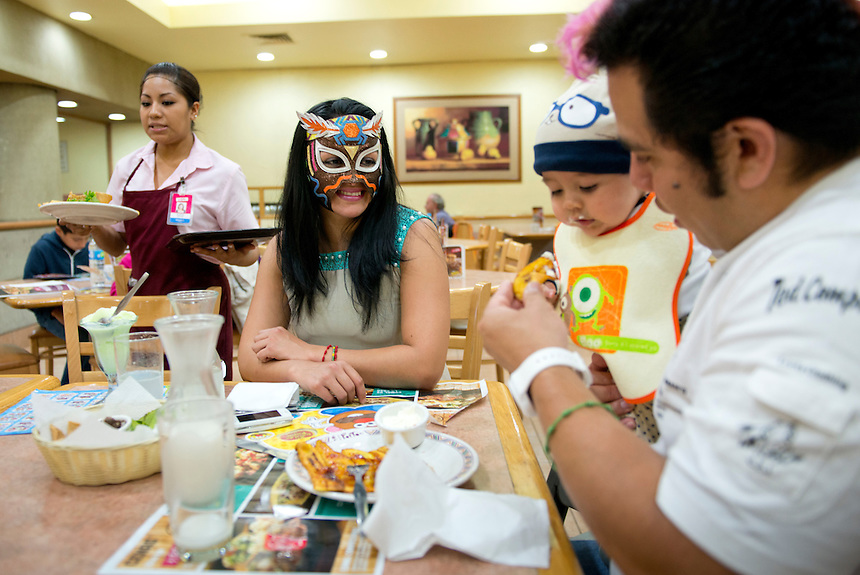 """At 9pm Maximo, a Lucha Libre wrestler who is an """"Exotico"""" meaning he fights as a gay Luchador has a quick snack of fried sweet plantains (platanos machos) with his wife India Siux and children at a restaurant before he enters the ring. Mexico City"""