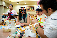 "At 9pm Maximo, a Lucha Libre wrestler who is an ""Exotico"" meaning he fights as a gay Luchador has a quick snack of fried sweet plantains (platanos machos) with his wife India Siux and children at a restaurant before he enters the ring. Mexico City"