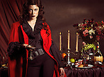 High fashion photo of a beautiful woman standing with a glass of wine at a table with remains of a festive dinner
