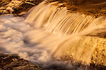 An image of golden water flowing over rocks at Eagle Falls at Lake Tahoe, Ca.