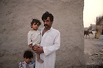 Marsh Arabs. Southern Iraq.  Marsh Arab man with daughter outside his adobe home banks of river Tigris. 1984