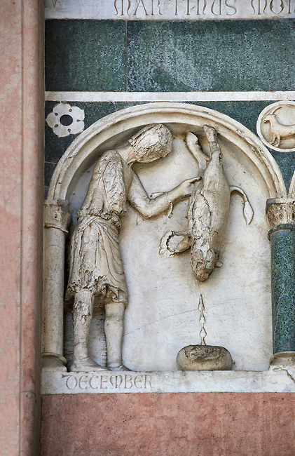 Late medieval relief sculpture depicting the labours for December with an animal being killed and astrological signs on the Facade of the Cattedrale di San Martino,  Duomo of Lucca, Tunscany, Italy,