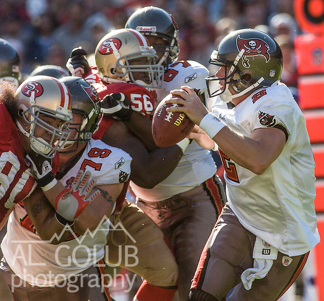 San Francisco 49ers linebacker Brandon T. Moore (56) and defensive tackle Isaac Sopoaga (90) rush Tampa Bay Buccaneers quarterback Brian Griese (8) on Sunday, October 30, 2005, in San Francisco, California. The 49ers defeated the Buccaneers 15-10.