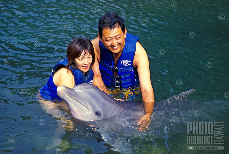Vacationers love to interact and pose for pictures with the Atlantic Botttlenose Dolphins in the lagoon of the Kahala Mandarin Hotel and Resort. Oahu.