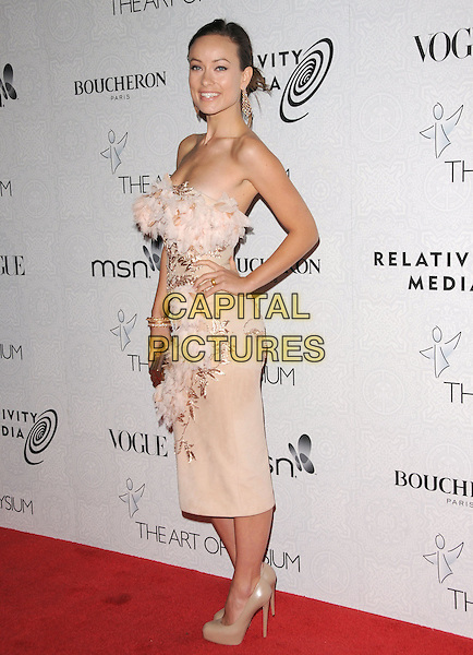"OLIVIA WILDE.Art of Elysium 3rd Annual Black Tie charity gala '""Heaven"" held at 990 Wilshire Blvd in Beverly Hills, California, USA, .January 16th 2010 .full length strapless cream pale pink beige nude textured dress clutch bag shoes platform patent gold silk chiffon embroidered pattern feathers feather Marchesa hand on hip .CAP/RKE/DVS .©DVS/RockinExposures/Capital Pictures"