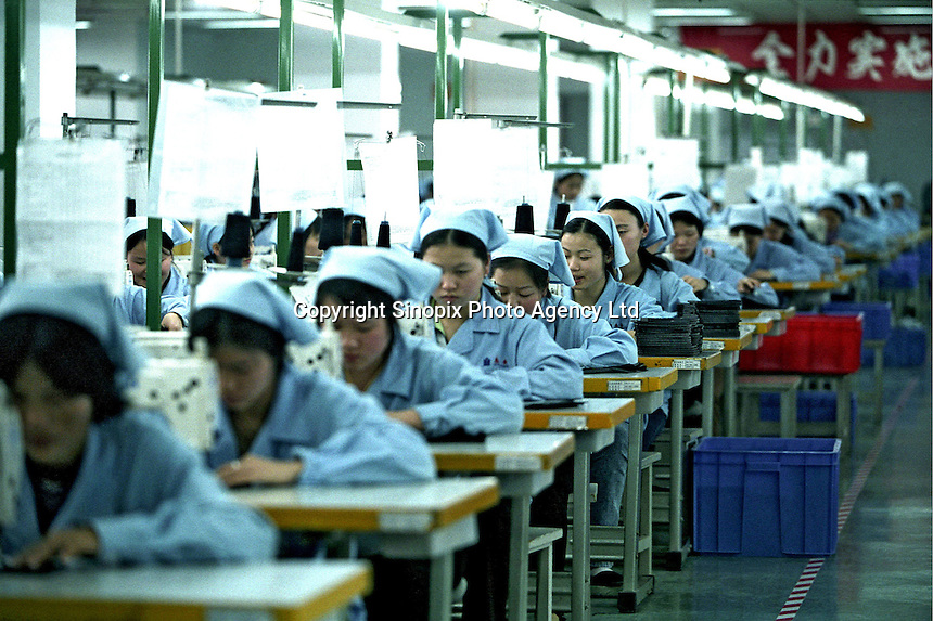 Factory workers use sewing machines at a factory in Guangzhou..17-JAN-03