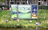Nederland Den Bosch  2016 . De Bosch Parade op rivier de Dommel. De Bosch Parade is een kunstevenement in 's-Hertogenbosch. De optocht bestaat uit varende kunstwerken. Alle werken zijn geïnspireerd op de kunst van Jheronimus Bosch. Mensen wachten op de vaartuigen. Op de achtergrond een schilderij van Bosch. Foto  Berlinda van Dam / Hollandse Hoogte