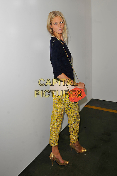 Poppy Delevigne .at House of Holland s/s 2013 catwalk show London Fashion Week LFW, NCP Car Park, London, England. .15th September 2012.full length black top gold shoes green trousers yellow print pink bag purse cropped blue.CAP/MAR.© Martin Harris/Capital Pictures.
