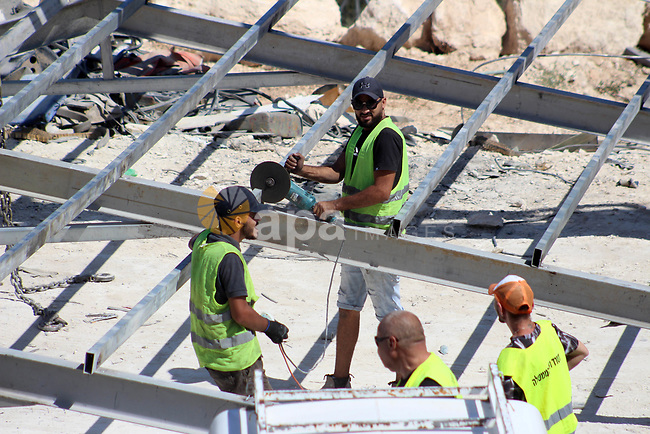 Israeli workers remove containers used as vehicles parking  which Israeli authorities said it was built without a permit in the West Bank town of Dura, south of Hebron on August 19, 2019. Photo by Mosab Shawer