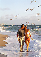 Young couple walking on the beach, with seagulls