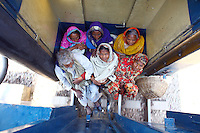 A group of passengers squeeze into a small space between two carriages on the outside of an inter-city train from Dhaka to Sylhet, about 350 kilometres away. In Bangladesh many people ride on the roofs of trains as frequently that is the only space available. For others, the fares are too high and can be avoided or reduced by travelling on the roof. However, this practice also leads to regular accidents, many of them fatal.
