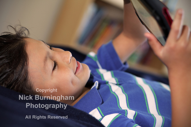 Young boy reading his tablet computer - EXCLUSIVELY AVAILABLE HERE