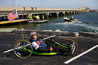 Morehead City, NC -- Portrait of quadriplegic hand cyclist Paul Kelly, 62, who trains for the Boston Marathon Tuesday, March 27, 2018. (Justin Cook for The Wall Street Journal)<br /> <br /> SUMMARY:<br /> <br /> Paul Kelly, hand cyclist, Beaufort, NC Training for the Boston Marathon so we would want to shoot in March to run the week before the marathon or marathon Monday, Apriln16. Life as a quadriplegic doesn't keep 62-year-old Paul Kelly on the sidelines. After breaking his neck in a swimming accident in 1978, Kelly was determined to find fitness activities to maintain an active lifestyle. He discovered handcycles while watching his niece compete in the 2006 Marine Corps Marathon and was inspired to start his own marathon career to stay fit. Paul has competed in over 100 half and full marathons. On April 16, he will celebrate his 40th year of living as a quadriplegic by taking on one of the most coveted races for a marathoner -- the Boston Marathon. Kelly is among the 60 handcyclists competing in the 2018 Boston Marathon with a qualifying time of 1:26:37. Most of Paul's distance training takes place at Bogue Banks, which includes Atlantic Beach, Salter Path, and Emerald Isle, N.C. It's Nicholas Sparks worthy scenery with its marshes, waterways, inlets and small islands. Paul is particularly fond of the approach from Atlantic Beach to Bogue Banks -- it's via the high-rise bridge. In cold weather, Paul has to be mindful of the environment and dress in a manner that insulates his legs while also allowing his upper body to ventilate. Paul chooses to train at times of day when the temperatures are more reasonable. He uses hand warmers in his gloves, on the inside the grips on his handcycle and in the legs of his trousers.