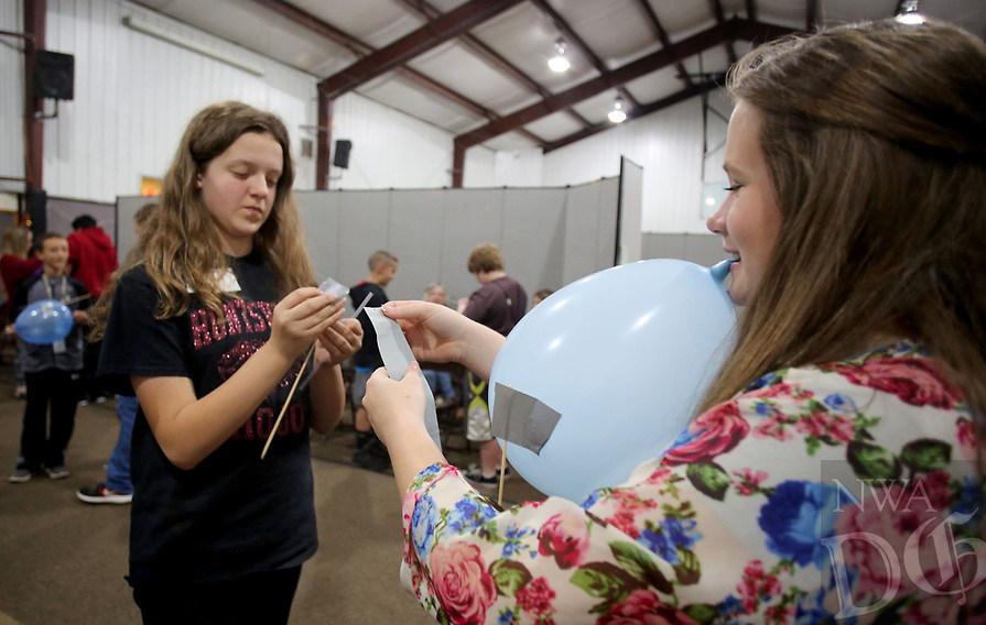 NWA Democrat-Gazette/DAVID GOTTSCHALK  Brielle Brasel (right), a sixth grade student at Huntsville Middle School, uses tape with Kelli Meythaler, also a sixth grade student, Monday, April, 17, 2017, to attach long wooden sticks to a balloon as they compete in the Balloon Joust during the Northwest Arkansas Science Olympian Tournament 2017 at Prairie Grove Christian Church in Prairie Grove. The two day tournament matches both elementary and middle school students from the area in events that include a Junkyard Challenge, Mystery Bridge and Marshmallow Catapult.