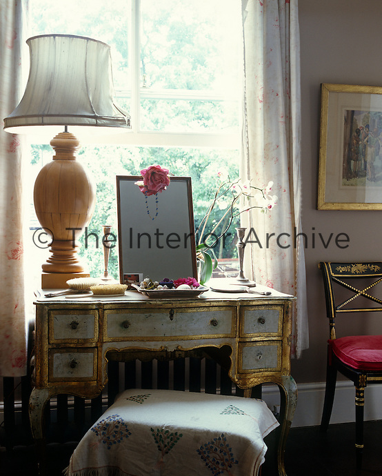 The dressing table in the window of the bedroom has been hand-painted and the outline of the drawers gilded