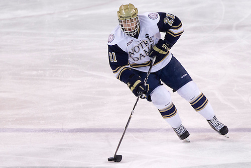 Notre Dame right wing Bryan Rust (#21) skates with the puck in third period action of NCAA hockey game between Notre Dame and Ohio State.  The Notre Dame Fighting Irish defeated the Ohio State Buckeyes 4-2 in game at the Compton Family Ice Arena in South Bend, Indiana.