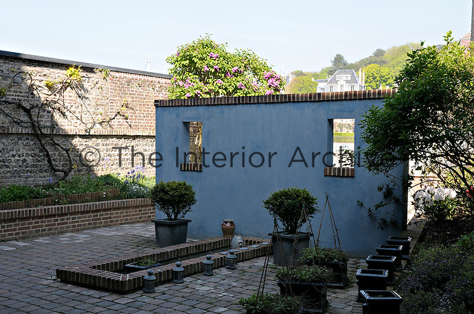 A free-standing partition wall of painted brick screens the courtyard garden from the harbour