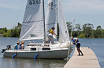 062410tvdocking.One member of the sailing class (right) helps nose the boat into proper docking position as the sailors come in off the lake for lunch.  When you dock a sailboat, you head straight into the wind, if possible, and someone else jumps out and eases the boat up against the dock and ties it off..BND/TIM VIZER