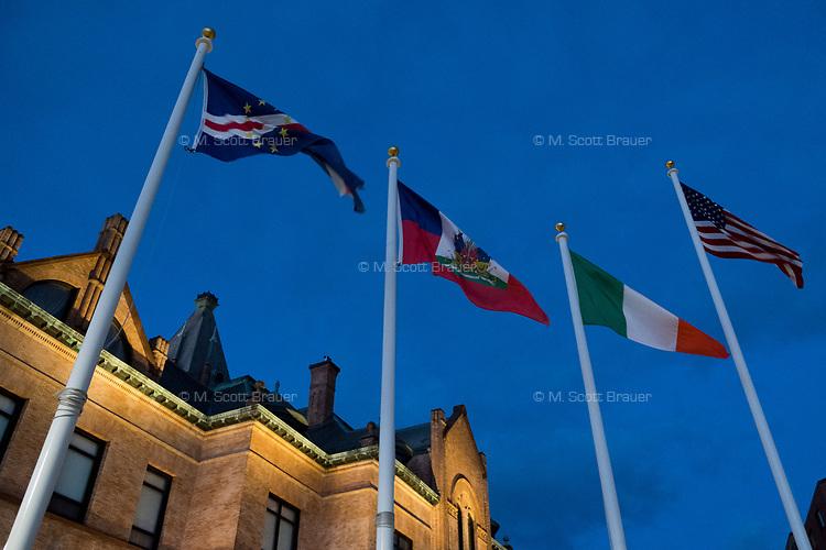 International flags fly near Brockton City Hall in downtown Brockton, Massachusetts, USA, on Wed., March 29, 2017.