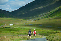 Couple walking through Hard Knott Pass in the Lake District National Park, Cumbria, UK