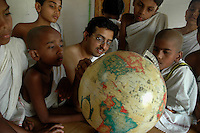 Students and teacher of  Om Shantidhama during a Geographical map pointing game class. Om Shantidhama is a residential vedic school for boys. Nestled among the confluence of hills, forest and rivers - Om Shanti Dhama is a world removed from the maddeningly fast and often chaotic urban India. Students from allover the country are selected to take part in its Vedic and free education system. What is unique about this institute is that they have blended the traditional and modern education system. Here computer and science is taught with the same passion as the Vedas and Shastras, helping the students to grow spiritually as well as earn a living. Bonding with the nature and animal world is a mandatory part of the institute's curriculum. Karnataka, India. Arindam Mukherjee