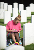 Sabrina Cradduck writes notes Friday, July 17, 2020, at the site of her husband, James Kelley Cradduck's gravestone at the Fayetteville National Cemetery. Cradduck visits the grave a couple of times a week since his passing in January. Cradduck leaves notes and prayers from herself and there daughter at the gravestone and also shares a penny and a prayer with other relatives buried at the cemetery. Check out nwaonline.com/200718Daily/ and nwadg.com/photos for a photo gallery.<br /> (NWA Democrat-Gazette/David Gottschalk)
