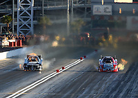 Mar 28, 2014; Las Vegas, NV, USA; NHRA funny car driver Cruz Pedregon (left) has a blower explosion racing alongside Chad Head during qualifying for the Summitracing.com Nationals at The Strip at Las Vegas Motor Speedway. Mandatory Credit: Mark J. Rebilas-